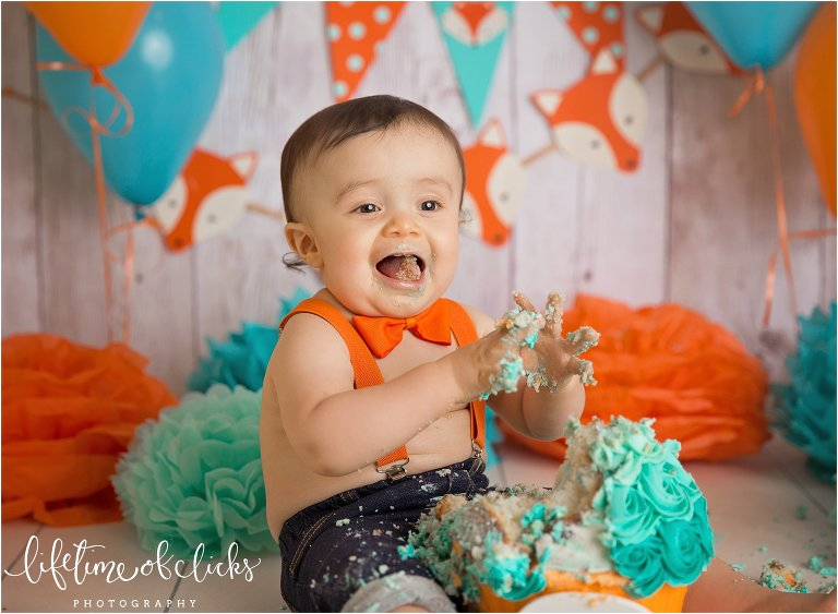 Happy little boy during cake smash by Lifetime of Clicks Photography