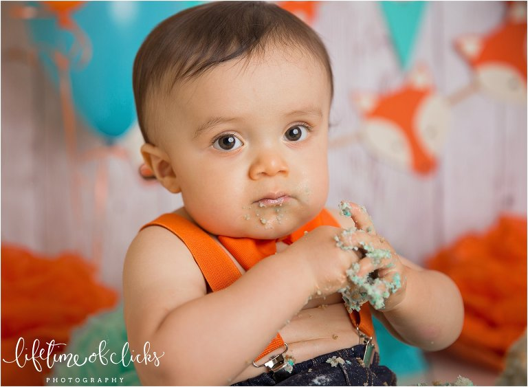 Little boy in orange suspenders cake smash session by Lifetime of Clicks Photography
