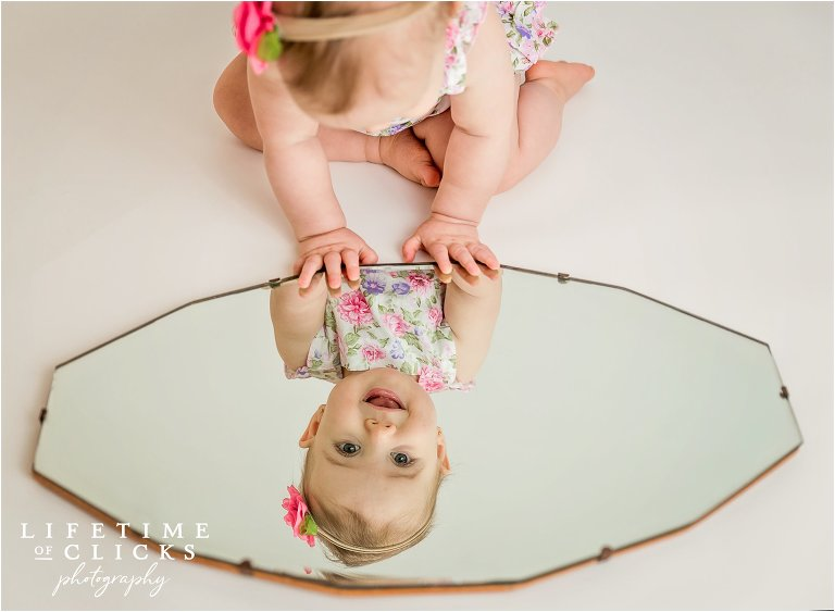 One year old looking at self in the mirror