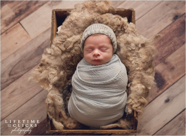 Newborn boy wrapped in gray and lying in a crate