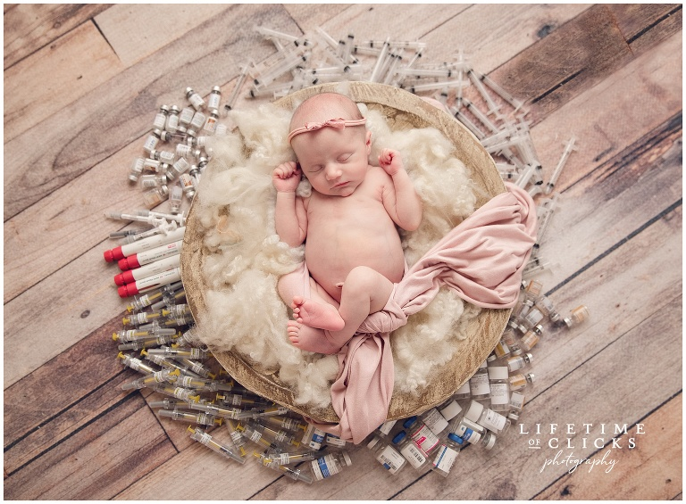 newborn rainbow baby photographed laying on wool and surrounded with IVF related medication