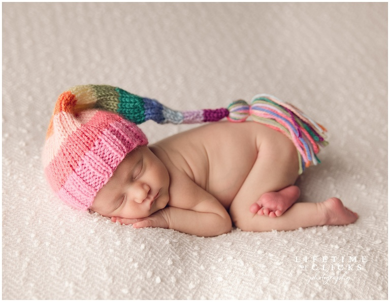newborn rainbow baby photograph with baby wearing a pastel rainbow hat