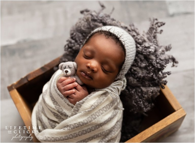 Newborn boy posed in a wooden crate