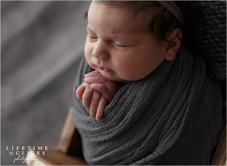 newborn girl wrapped in gray blanket