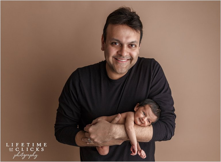 smiling newborn in father's arms