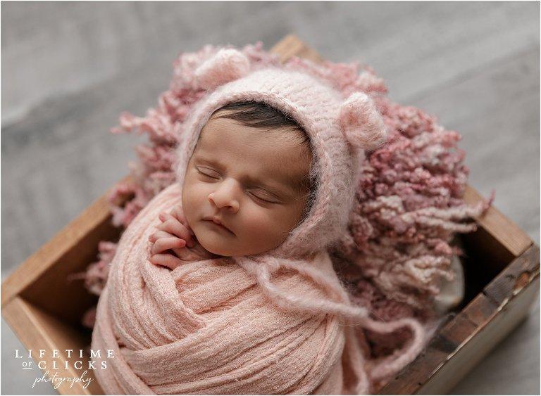 newborn girl wearing pink bear hat