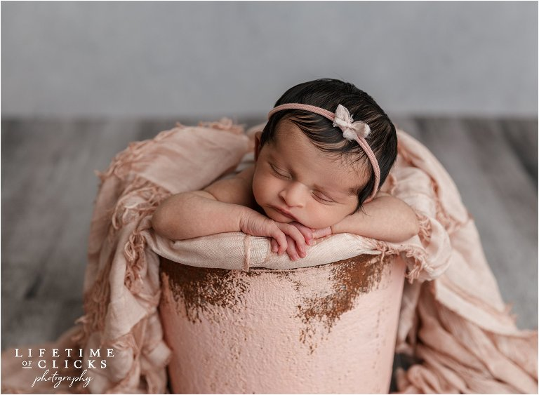 newborn girl in pink bucket