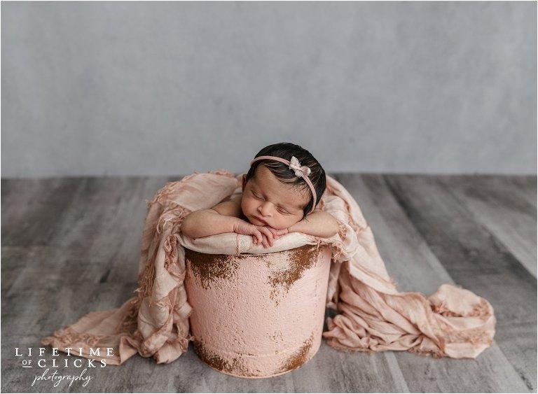 newborn baby girl posed in pink bucket