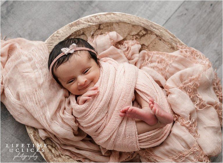 smiling newborn wearing pink wrap