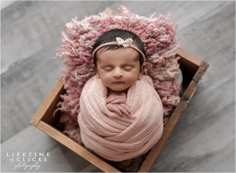 posed newborn in a wooden crate