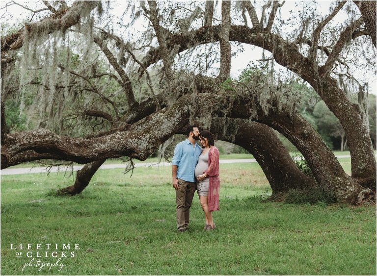 engaged couple posing for maternity photos under a moss covered tree